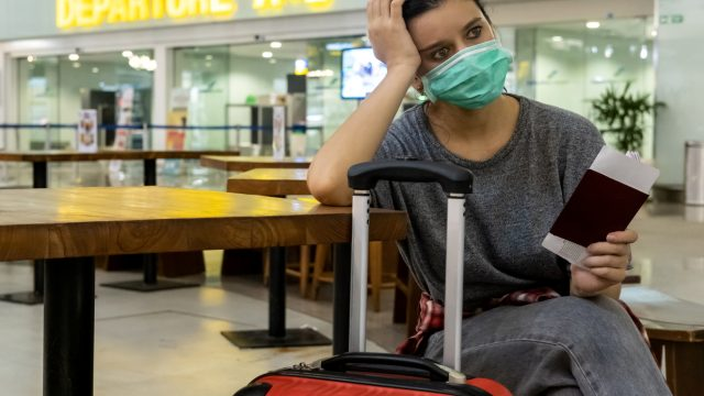A female traveler sitting with her luggage looking distressed