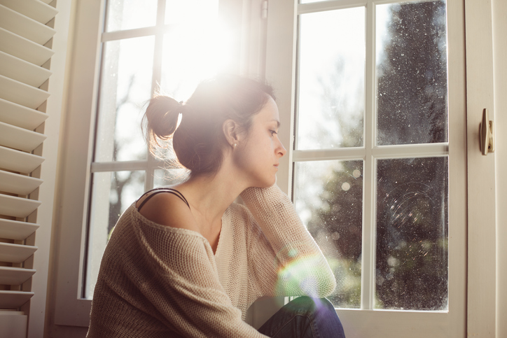 A Caucasian woman sits at a window with a strained look on her face