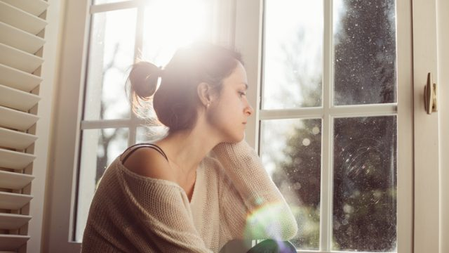 Woman sits at a window with a strained look on her face