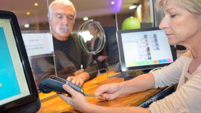 White female bank teller running credit card