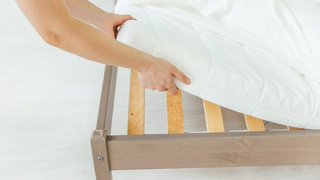 white hands putting sheet on bed