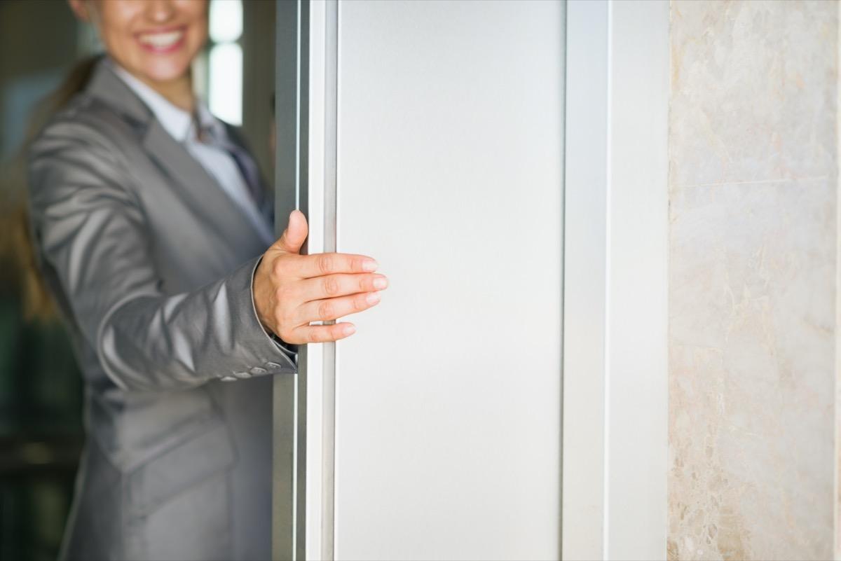 white woman holding door open