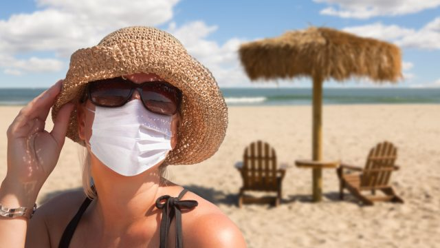 A woman in sunglasses and a hat wearing a face mask on a sunny beach