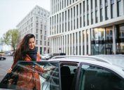 Young commuter woman catching a car ride share service in Berlin. She is smiling, wearing a fashionable coat, entering the vehicle.