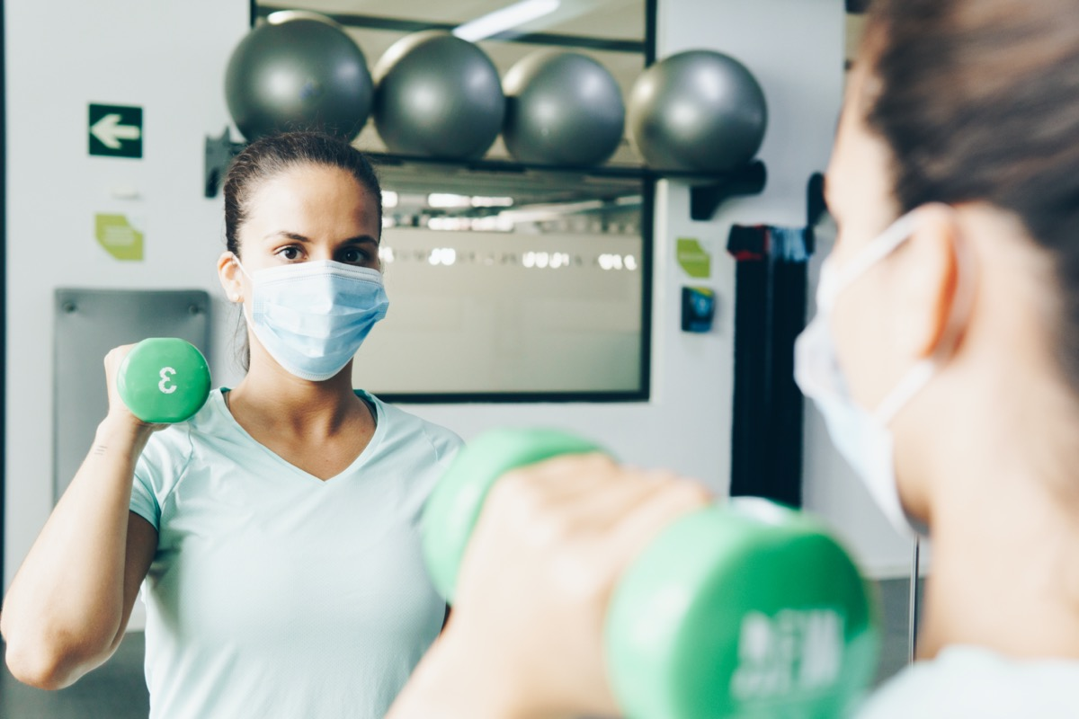 woman lifts gym weights in a gym with a mask on