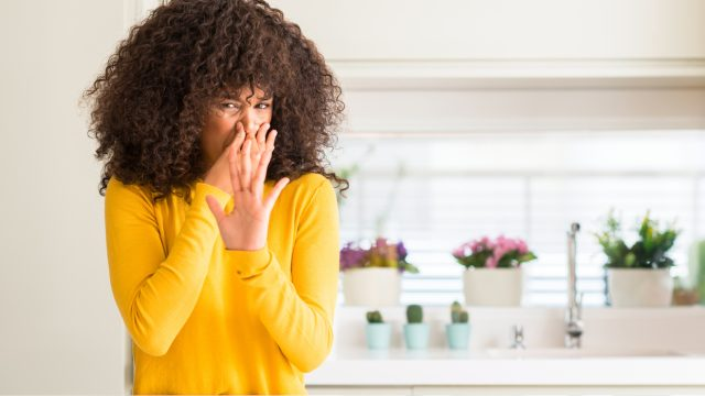 African american woman wearing yellow sweater at kitchen smelling something stinky and holding her nose