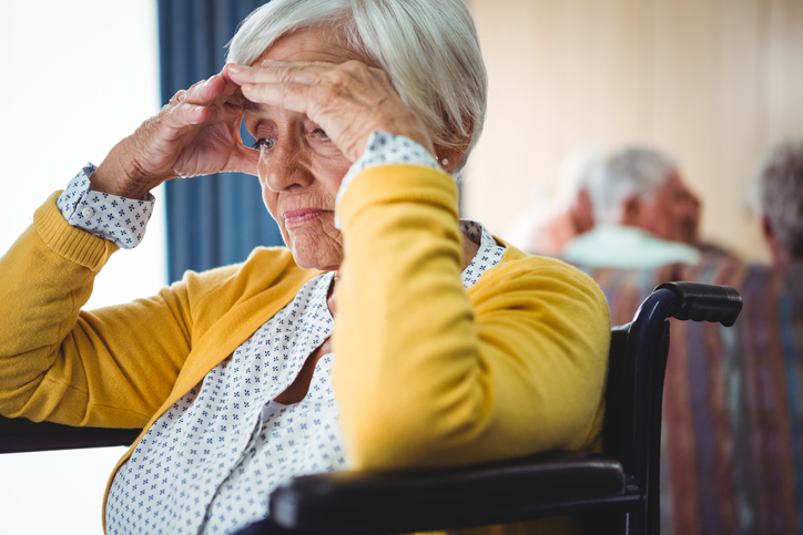 A senior woman sitting in a wheelchair holding her head looking confused and worried