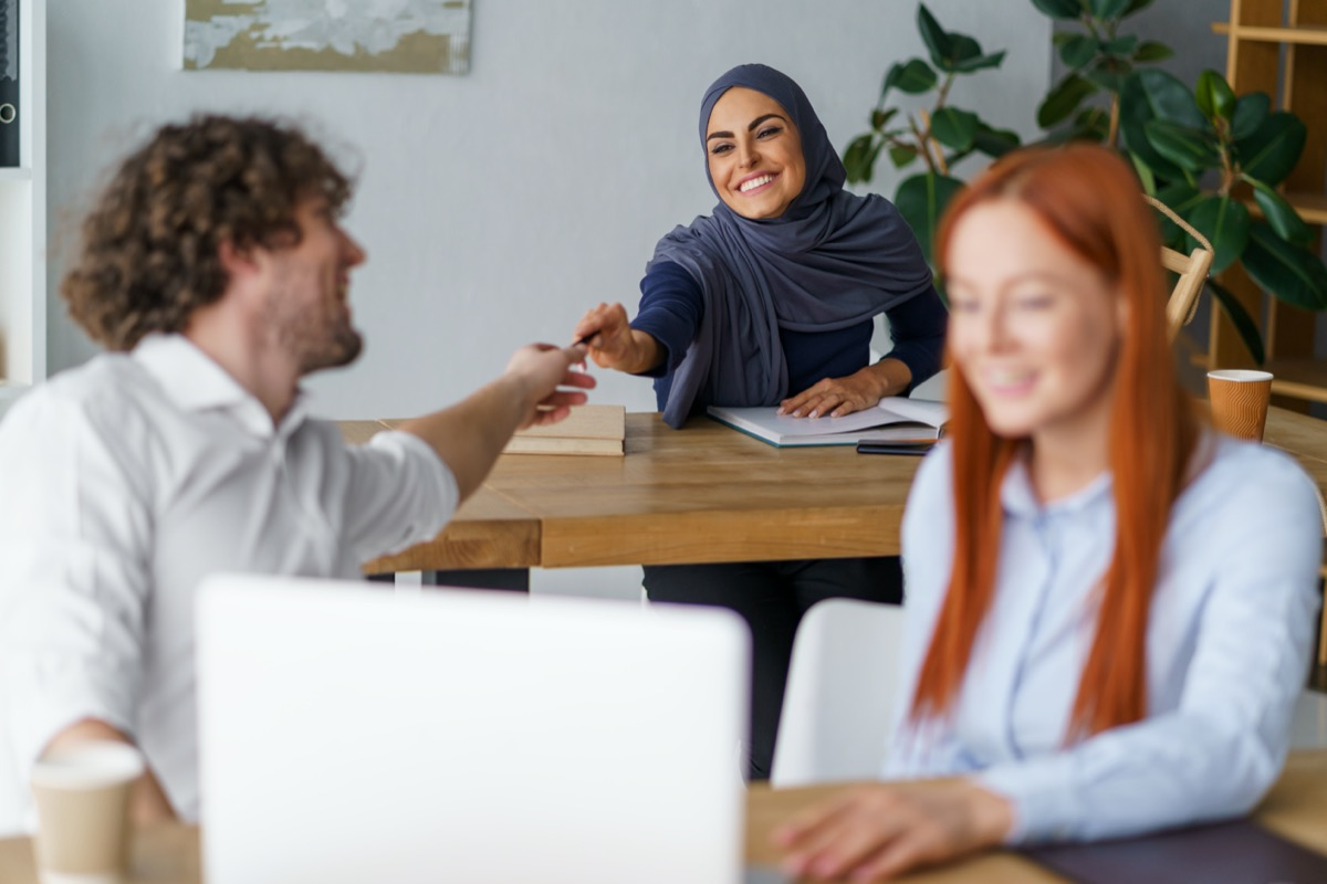 woman in hijab lending white male coworker a pen