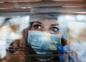Worried Woman looking through window while wearing a surgical mask