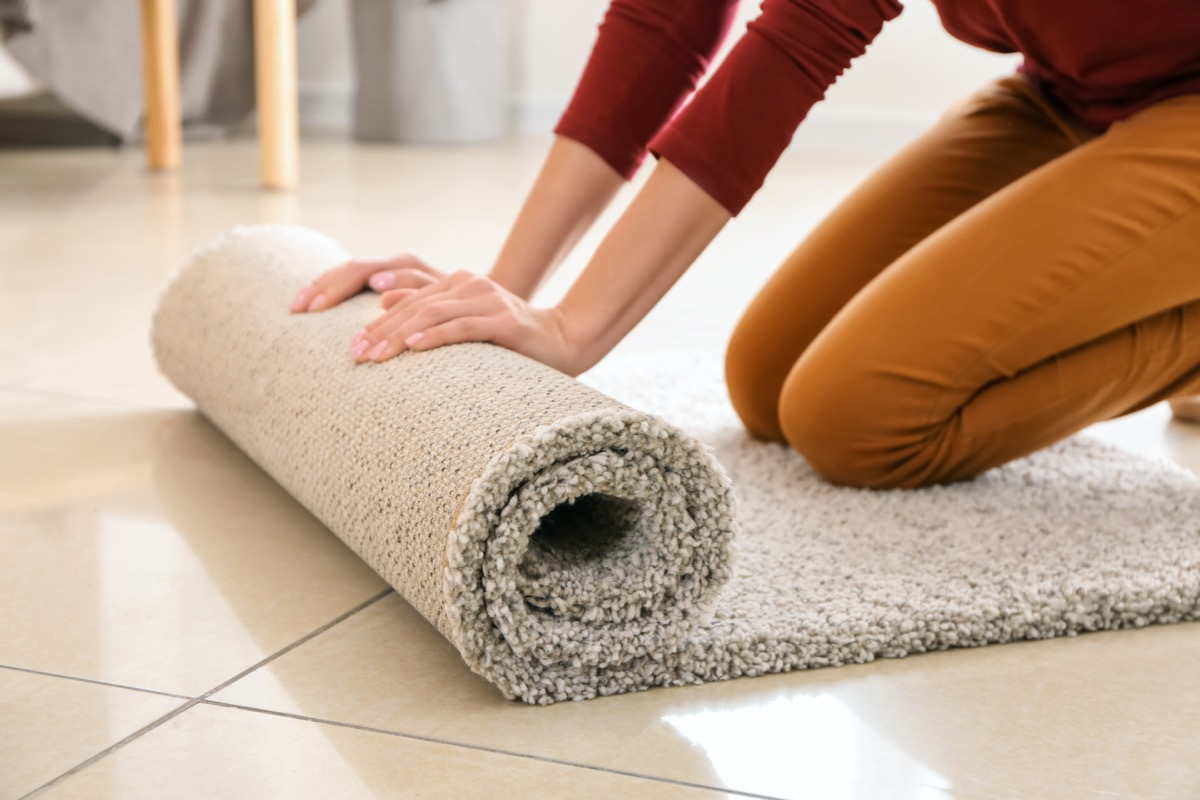 white woman rolling out shag carpet