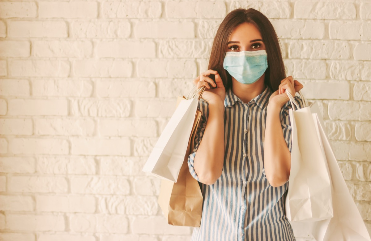 Happy girl shopper in protective face mask with paper bags in hands. Young woman in medical face mask holding shopping bags. Girl shopaholic in mall. Sale, discount, coronavirus COVID-19, copy space