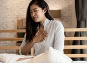 An Asian woman sitting in bed with her hand on her chest showing difficulty breathing