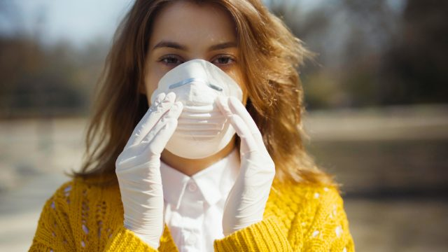 A young caucasian woman in a yellow sweater wearing latex gloves and a face mask