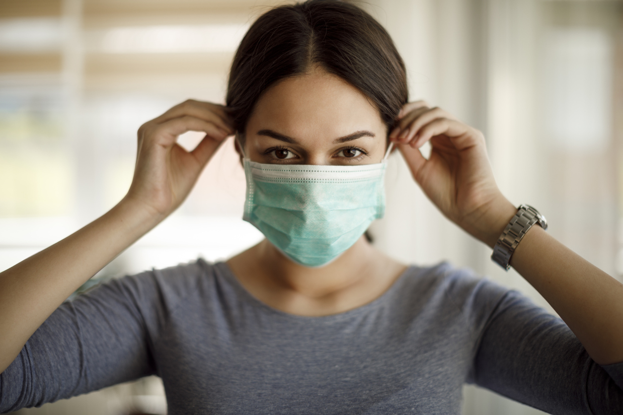 A young woman putting on a protective mask