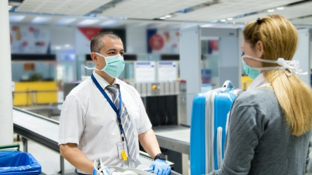 white woman wearing mask at airport security