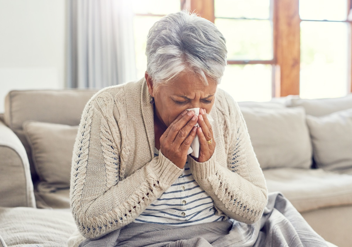 Shot of a sickly senior woman blowing her nose with a tissue while sitting on a sofa ta home