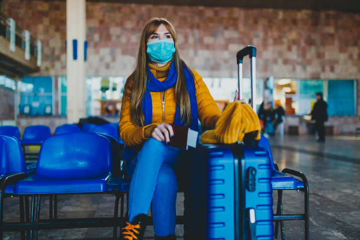 A woman wearing a face mask sits next to her blue suitcase in a travel lounge