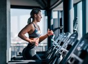 Side view of muscular woman running on treadmill.