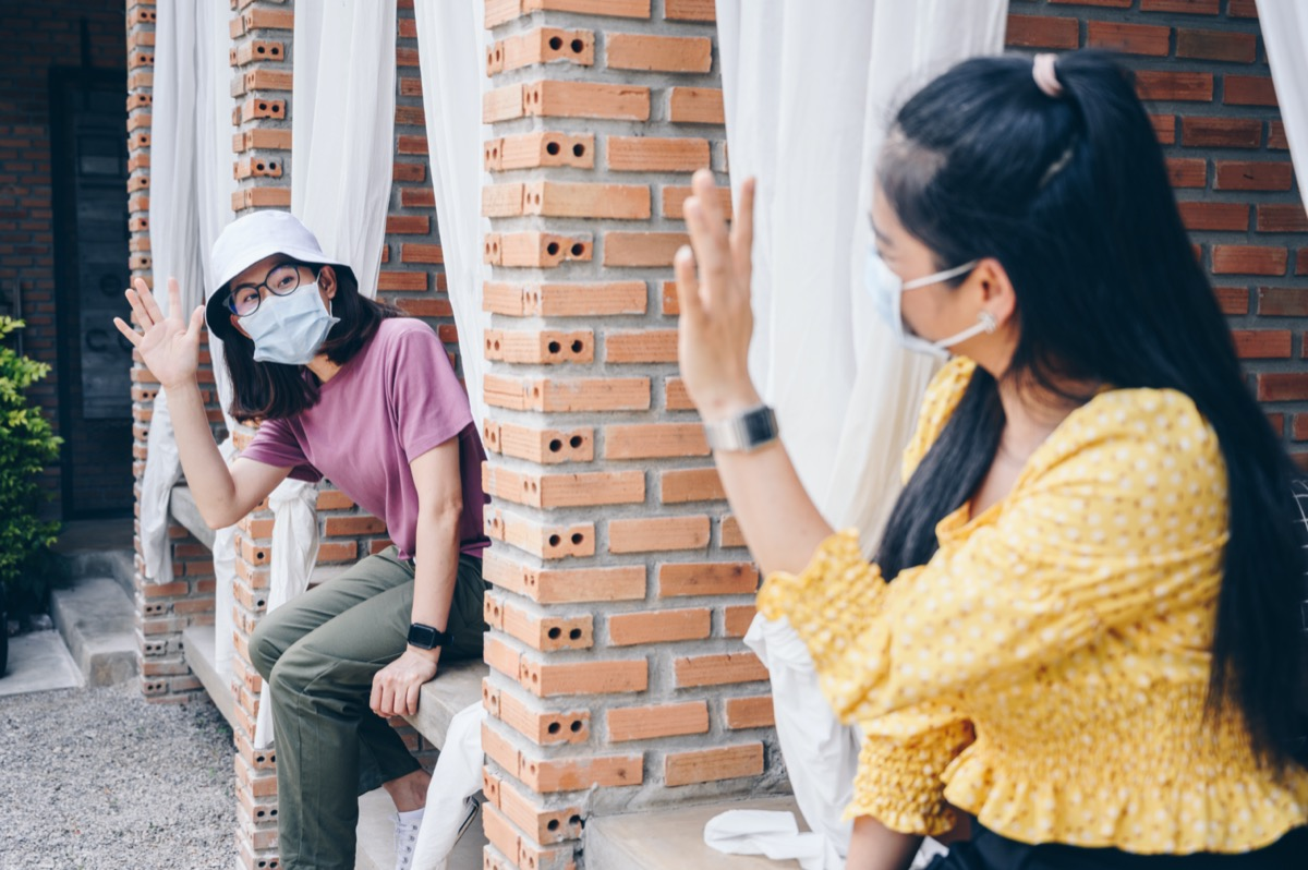 young asian women waving at each other while wearing masks
