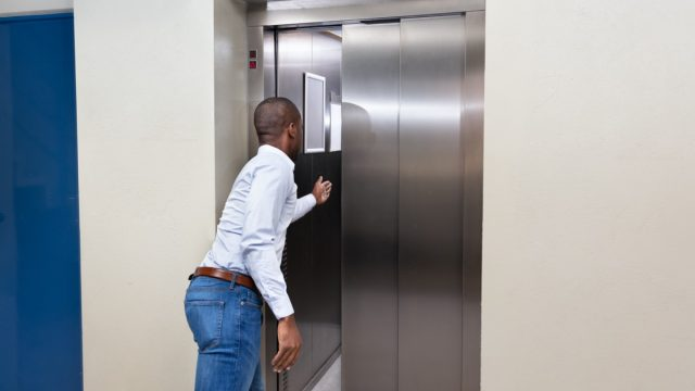 young african american man trying to hold elevator door