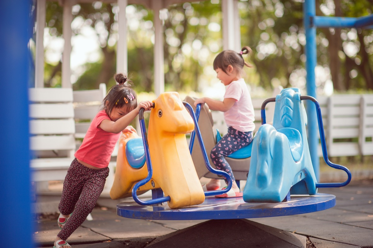 two young asian girls playing on playground