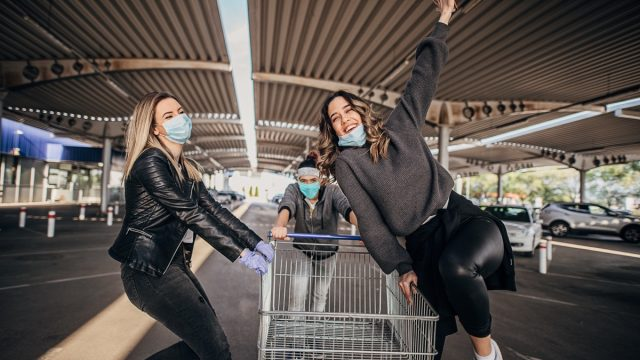 Three young friends with protective masks and gloves having fun in shopping after coronavirus lockdown.