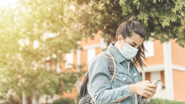 Young woman with surgical mask traveling around the city
