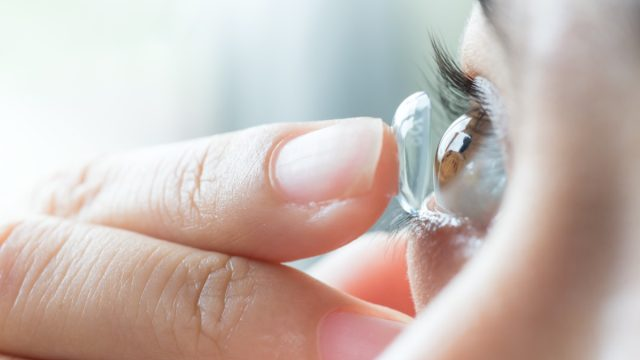 young woman putting contact lens into eye