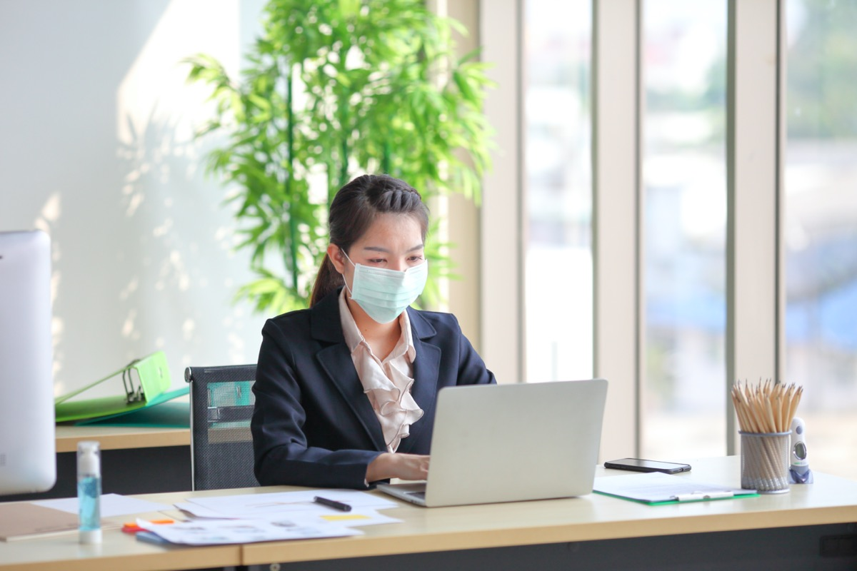 young asian woman wearing face mask at work
