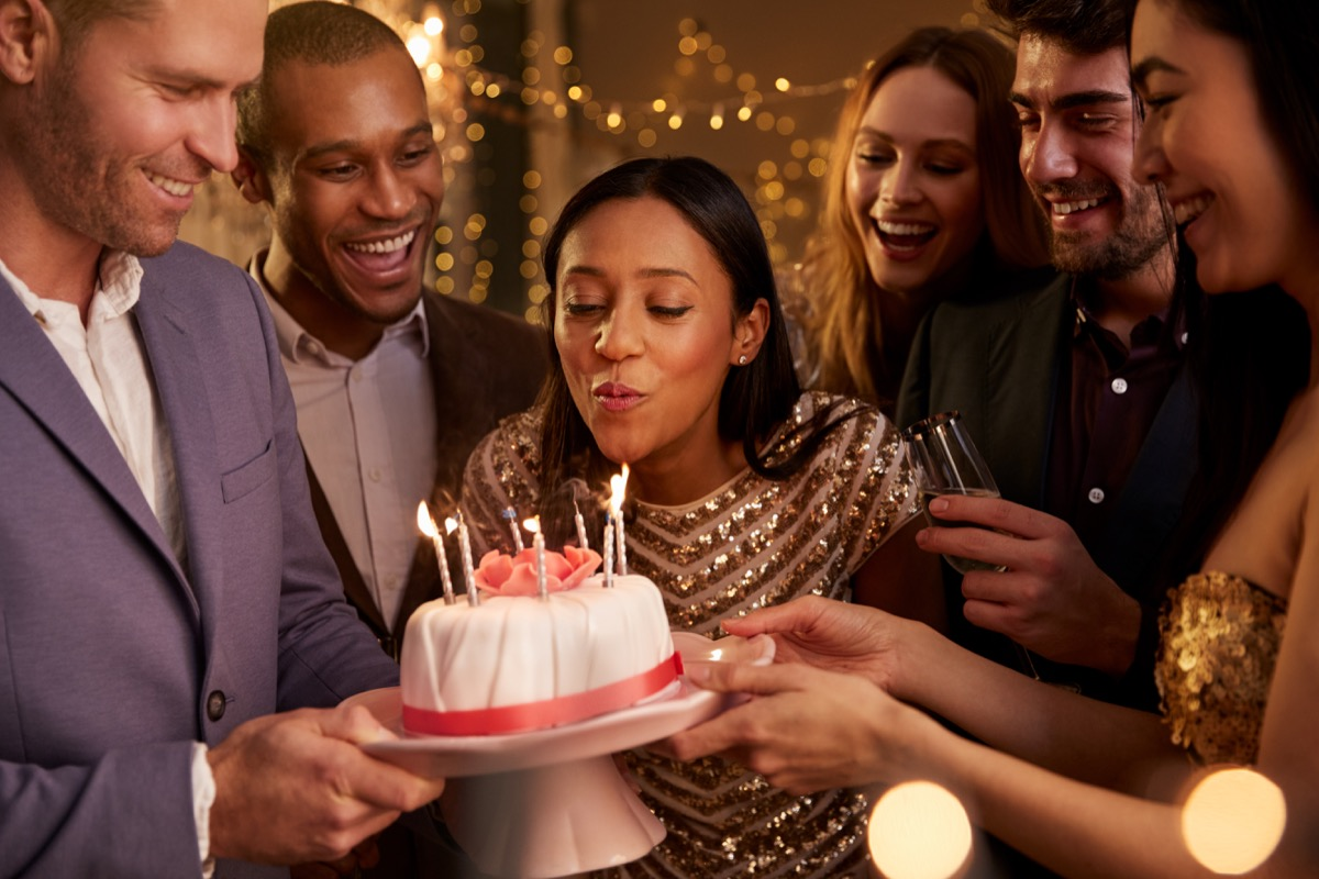 Woman blowing out candle at birthday