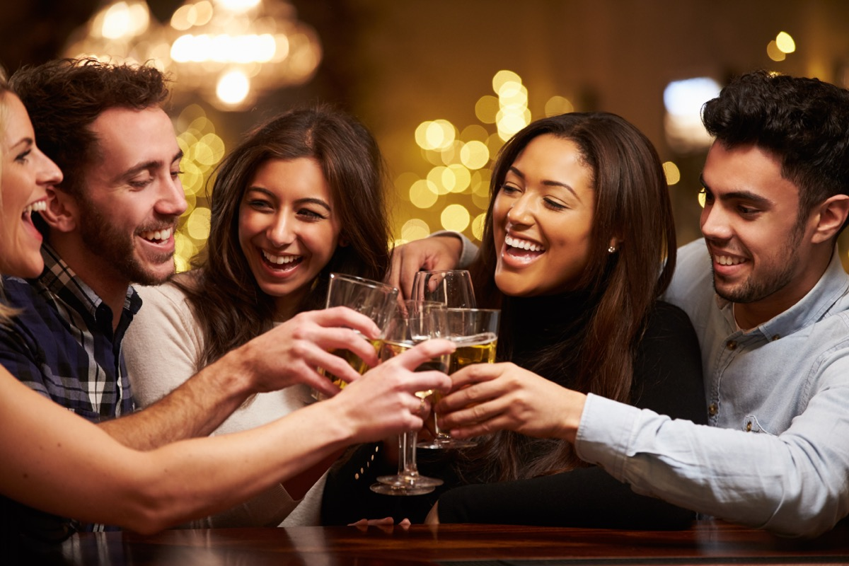 Friends drink and laugh at bar