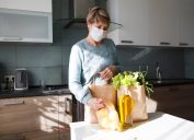 Older woman unpacking groceries with mask on