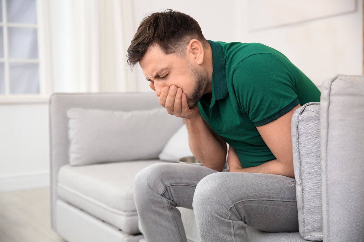 Man on couch feeling nausea