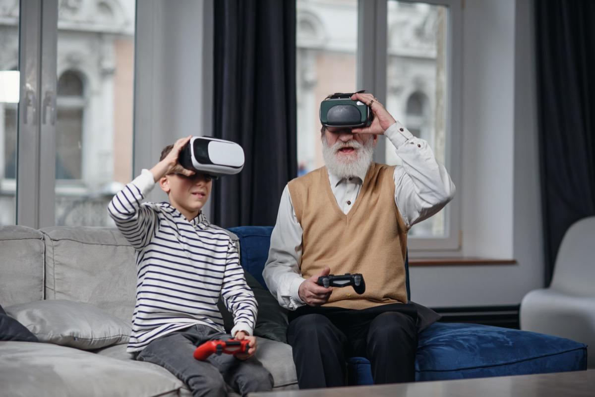 Senior man and boy playing virtual reality game