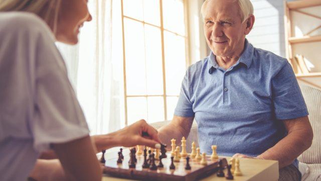 Senior white man and young woman playing chess