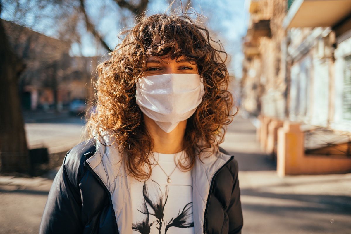 Young woman with mask on outdoors