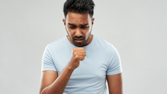 Young man coughing into fist
