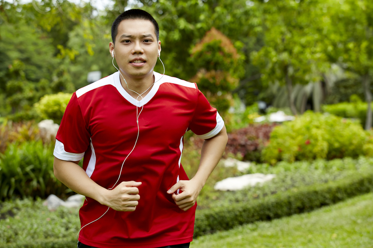 asian man running with headphones in ears, wearing red sports jersey shirt