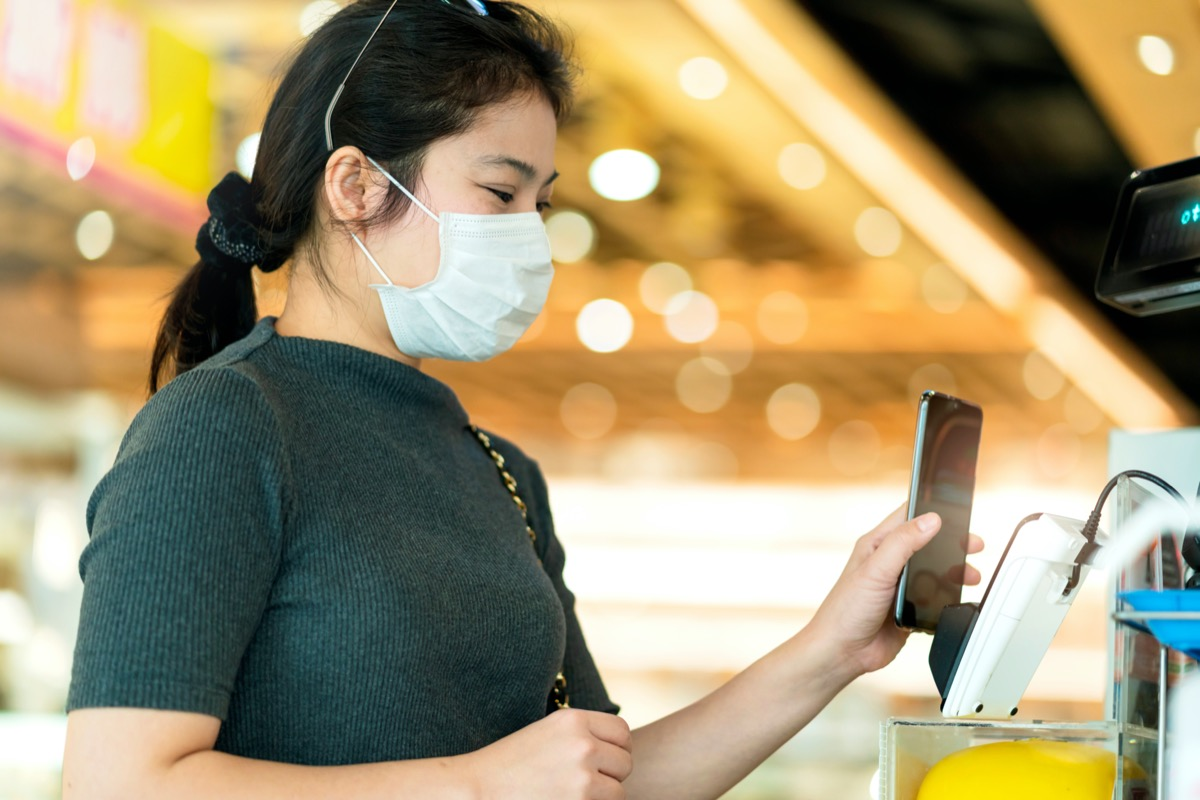 young asian woman in mask using phone to pay
