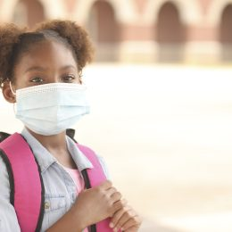 Black girl on school campus wearing a mask for coronavirus protection.