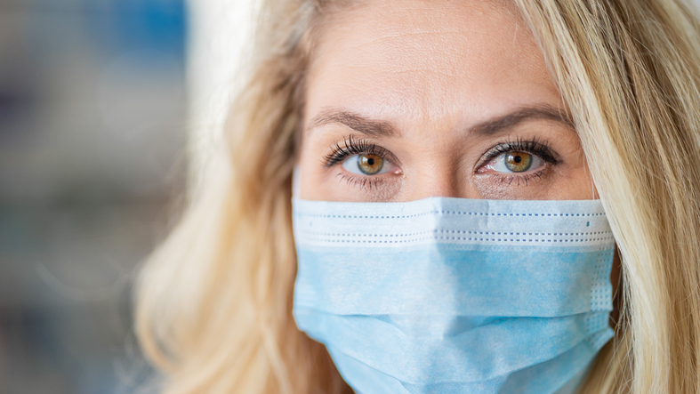 A blonde woman wearing a face mask to stop the spread of coronavirus