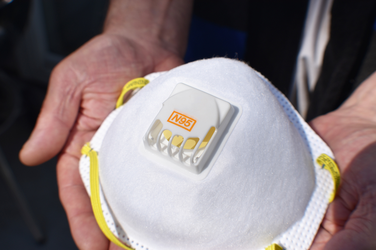 A close up of an N95 respirator protective face mask being held in someone's hands