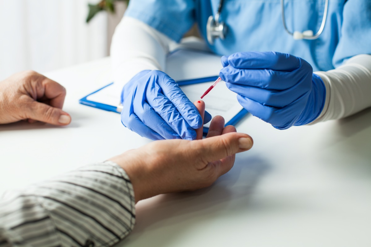 white hand getting blood draw for coronavirus from doctor or nurse wearing gloves