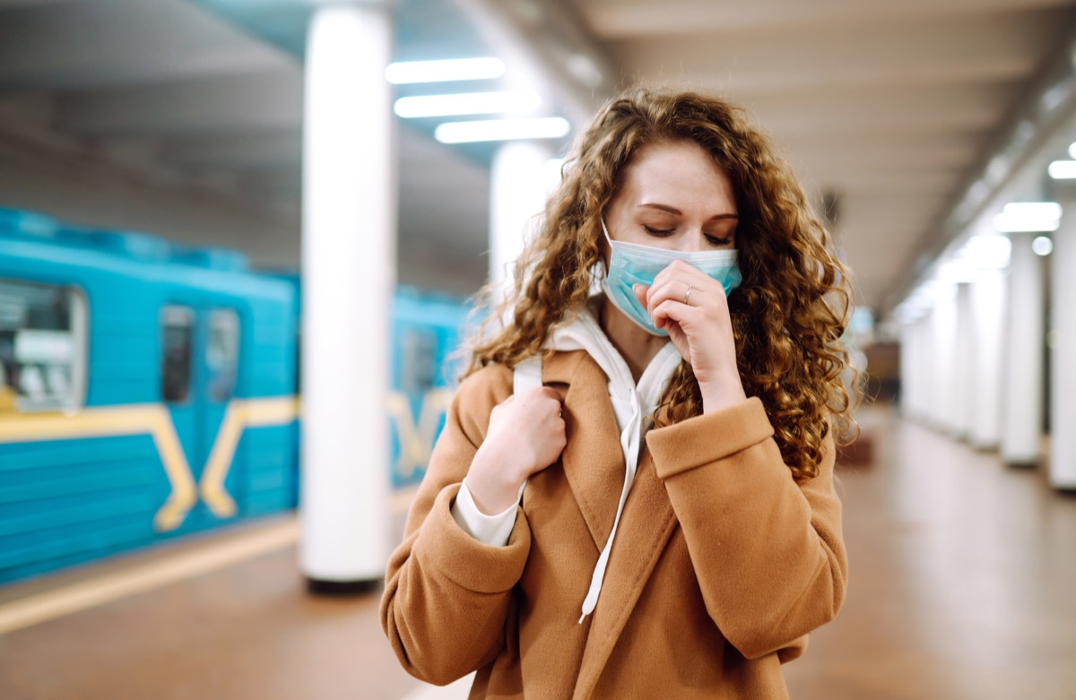 Woman coughing wearing a mask in subway station