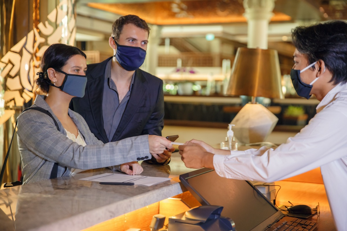 couple wearing face masks checking in with hotel concierge