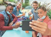 two young men and two young women take a selfie while dining outside amid coronavirus. their masks are resting on their chins.
