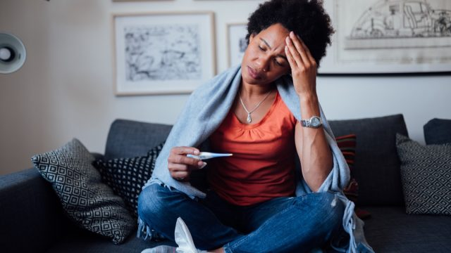 Worried woman sitting at home while being sick