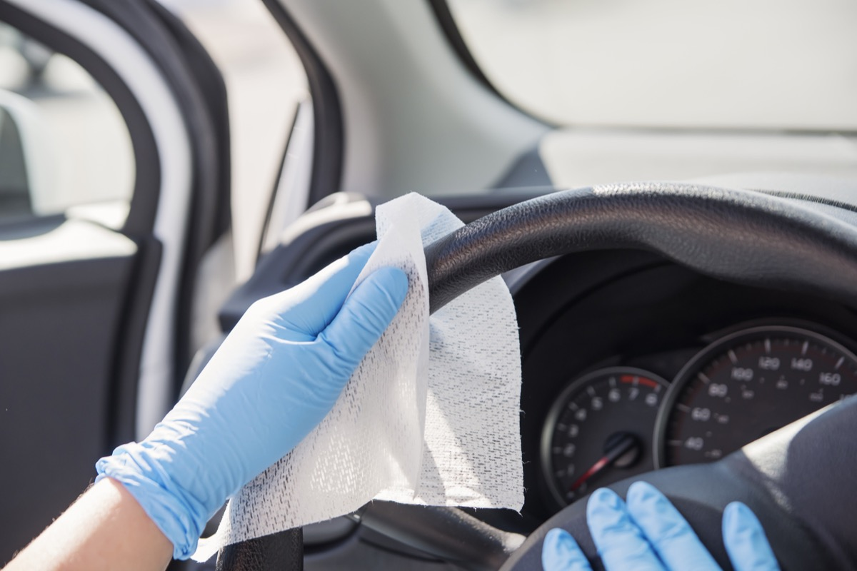 Female hands with blue glove wiping car steering wheel with disinfectant wipe. Horizontal outdoors close-up with copy space.