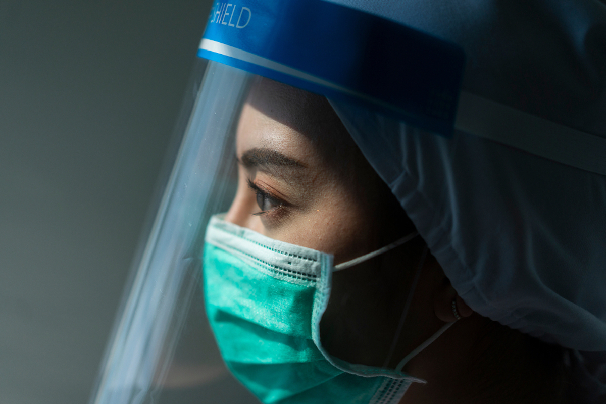 doctor looks stressed in mask and face shield amid coronavirus