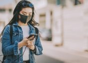 a young girl tourist wearing a face mask while texting